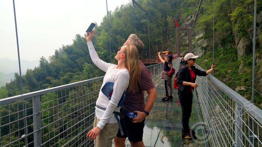 白水湾高空玻璃桥景区位于安徽省安庆市潜山县天柱山镇白水村,自2017年11月18日建成对外开放以来,吸引了不少本土及周边城市游客,由于此处玻璃桥与其他景区玻璃桥、玻璃栈道有不同亮点,能行走在玻璃桥上近距离观赏瀑布,又能感受玻璃桥的晃动带来前所未有的刺激,景区除了有瀑布、花海、玻璃桥,还有极限挑战的悬崖秋千,令多少坚强女子在晃荡的过程中放声尖叫。景区自开园至今,游人慕名纷纷而来,今年清明小长假,吸引了众多省内外及国外(俄罗斯、伊朗等地)游客前来观光游览,因小长假前下了小雨,景区景色绿得格外清新,青山银练,红